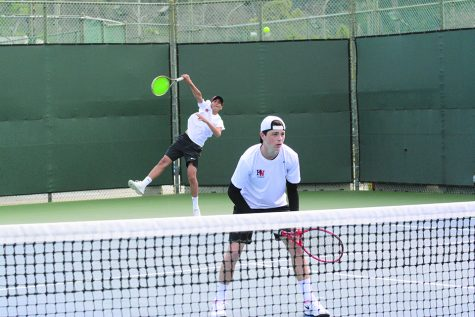 DUAL THREAT: Doubles player Avi Carson '22 prepares for the opposing team to return Amaan Irfan's '21 serve Feb. 27. Photo credit: Lucas Lee/Chronicle.
