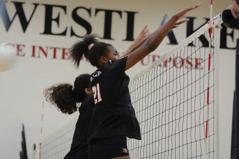 BLOCKERS: Kennedy Hill '22 and former senior member Lauren Juzang '19 try to do a block in order to deflect the spiked ball back to the other side. Hill said that the team will practice more and more to not only improve but also achieve a perfect season. Credit: Caitlin Chung/Chronicle.