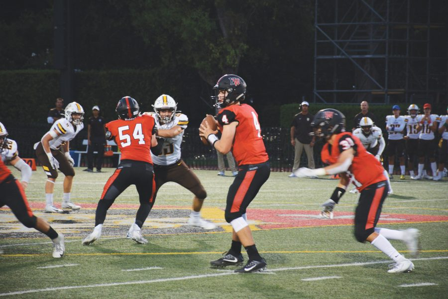 Quarterback Marshall Howe '21 drops back in the pocket, surveying the field for an open receiver on the left sideline. The Wolverines lost to Crespi Carmelite High School 54-0 Sept. 6 after defeating Venice High School on Aug. 30. Credit: Eugean Choi/Chronicle