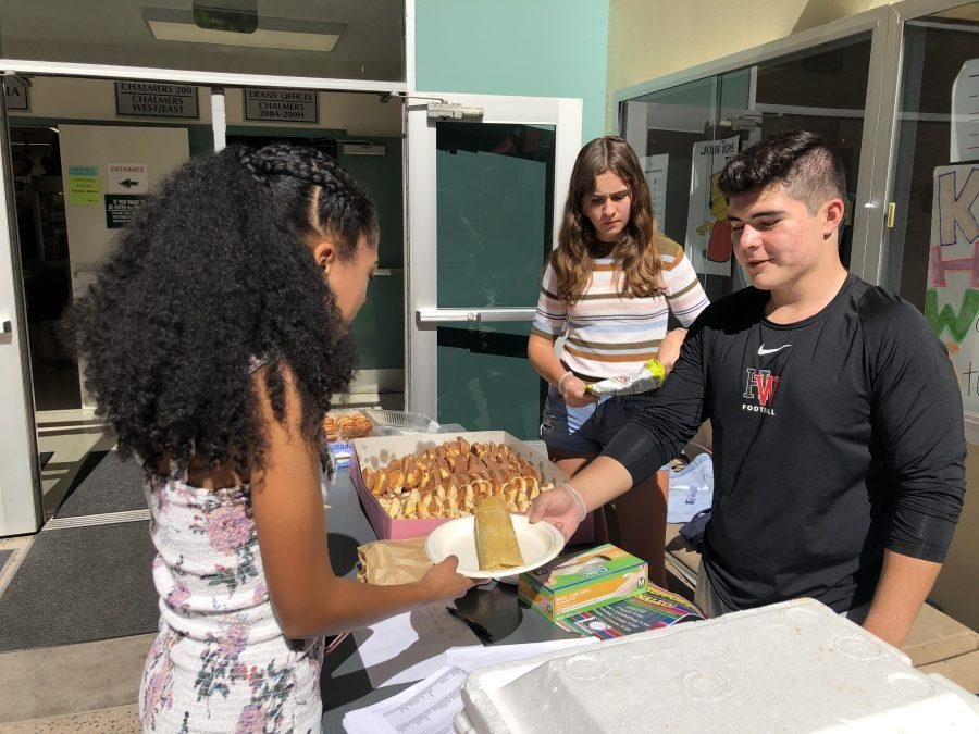 LAHSO member Josue Martin '20 hands a tamale to Isabel Lawrence '21 on the quad during the fundraiser. Credit: Hannah Han/Chronicle
