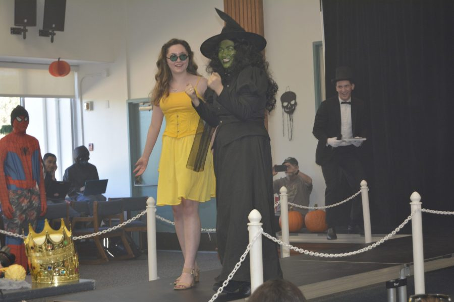 "Best overall costume winners Emery Genga '21 and Felicity Phelan '21, dressed as Glinda and Elphaba from ""Wicked,"" walk down the runway in the lounge. Credit: Ethan Lachman/Chronicle"