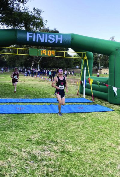 Runner Nathan Aloisi '20 crosses the finish line in the Mission League Meet Final at Crescenta Valley Park. Chloe Schaeffer/Chronicle