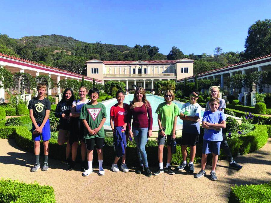 (From left to right) Franklin Wimbish '25, Addison Konwiser '25, Maddie Hliboki '25 and Chazzy Cho '25 pose for a photo with the rest of their Latin IA peers in front of the Getty Villa's long pool. Credit: Sandra Koretz/Chronicle