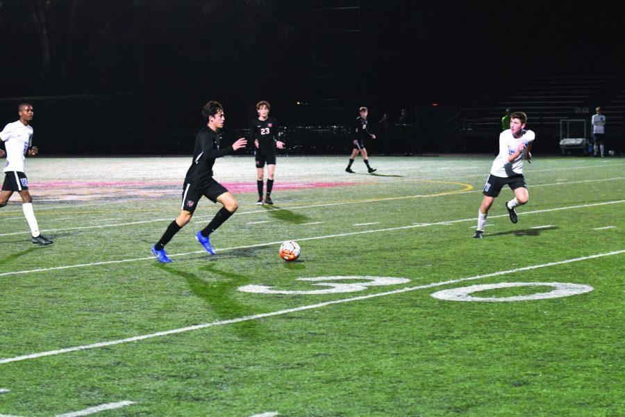 Midfielder Pablo Greenlee '20 dribbles the ball ahead in the 4-0 win against Windward High School on Friday. Greenlee scored the fourth goal for the Wolverines late in the second half. Credit: Charlie Wang/Chronicle