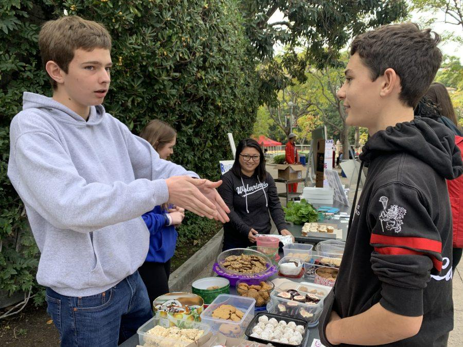 Stephen Purdum '22 sells baked goods to Micah Gold '22 on the lower quad. Friday while explaining that proceeds from the bake sale will be donated to the Rainforest Action Network.
