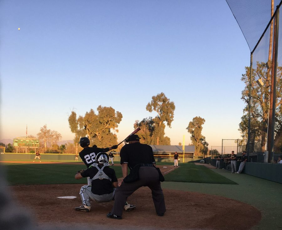 Catcher Jacob Galloway '22 drives a pitch to the outfield against Mira Costa High School on Feb. 20. The Wolverines would win that game 11-3.