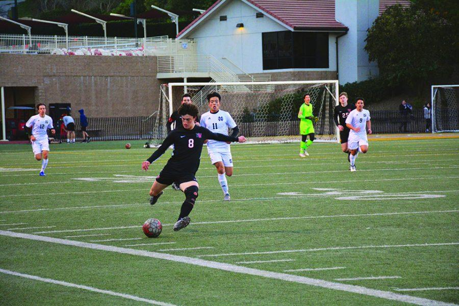 GABE GOT GAME: On Senior Night, midfielder Gabe Palacios '20 passes the ball as forward Eric Guo (NDHS '21) trails behind. The game ended in a 2-2 tie Feb. 3, marking the last time that the 11 seniors suited up in the regular season on Ted Slavin Field.  Credit: Eugean Choi
