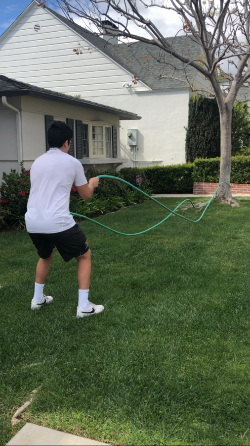 Linebacker Spencer Felix '21 uses a hose as a replacement for ropes while working out at home during the quarantine period. Printed with permission of Spencer Felix.