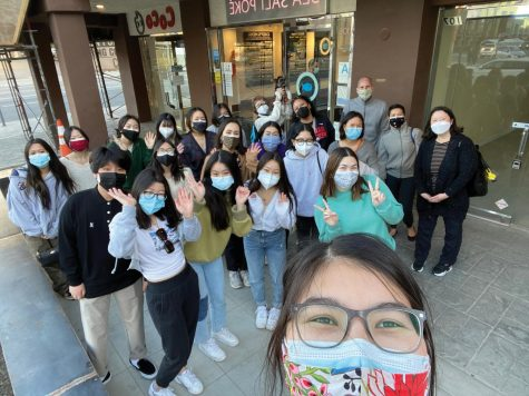 Students wearing masks pose in front of a storefront on Sawtelle Boulevard.