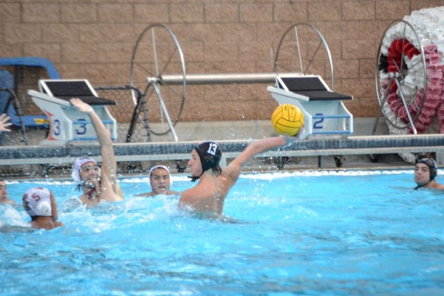 Boys' water polo player Jaxson Tierney '23 sets up to shoot the ball in the face of numerous defenders.