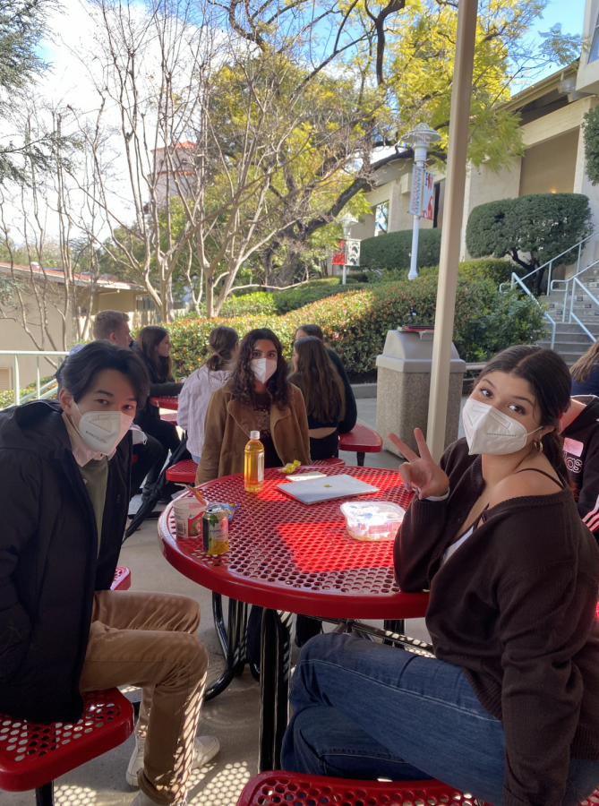Billy Johnson '22, Charlotte Massey '22 and Shanti Hinkin '22 pose for a photo together while socializing and eating at table in front of the newly built cafeteria annex.