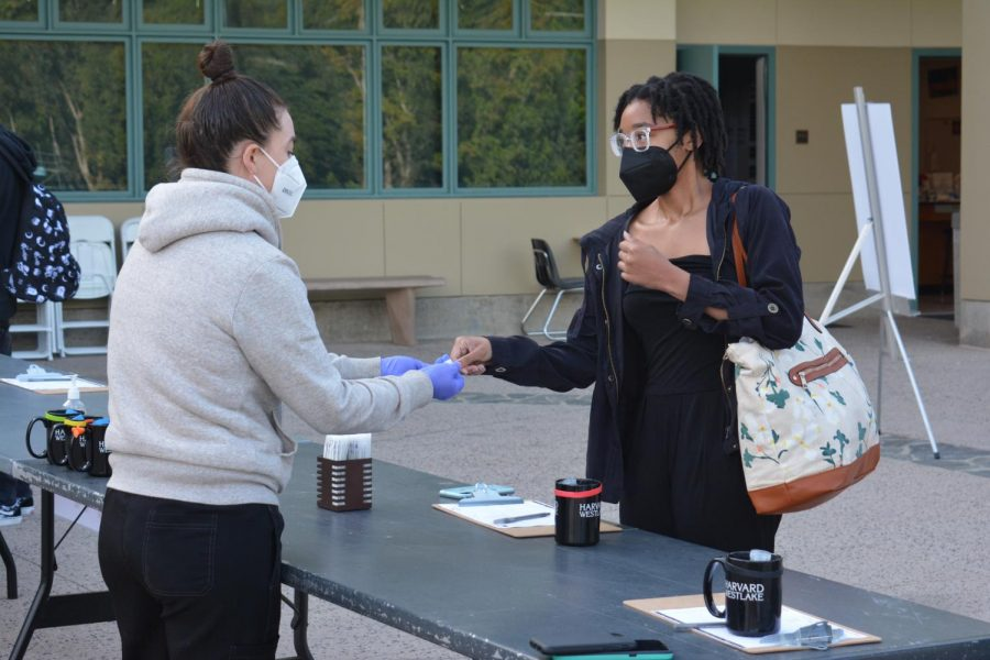 Chandace-Akirin Apacanis '21 gives her nasal swab to Upper School Nurse Becca Pilgrim before class outside of the Munger Science Center in adherence with school COVID-19 protocols.