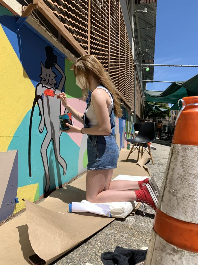 Eva Salas '22 works on part of the mural at Crete Academy with visual arts students.