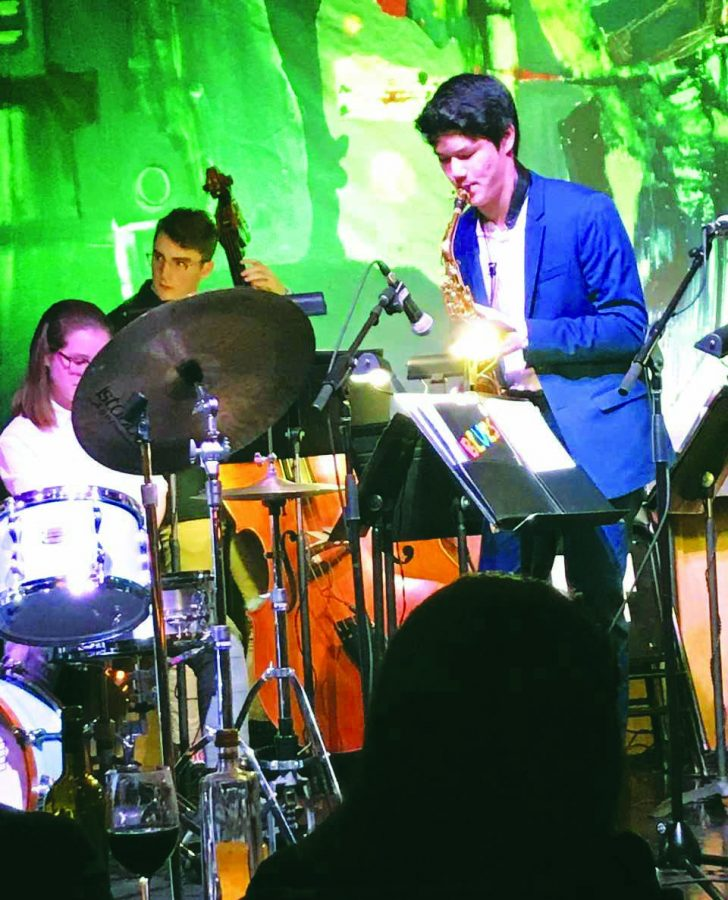 The spotlights focus in on Brandon Liang '21 as he performs onstage with the school's Jazz Band.