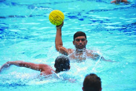 Shooting into season: Jack Burghardt '23 winds up to gather power before shooting the ball between two defenders in the team's pre-season training. Boys water polo looks to start its season off strong in its Mission League home opener against St. Francis High School on Aug. 25.