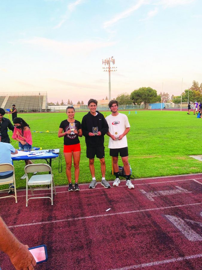 First to Finish: Following the first race of the season, Daniela Quintero '22 and Print Managing Editor Will Sheehy '22 lift first place trophies for the girls and boys divisions, respectively, at the Gahr High School Race.