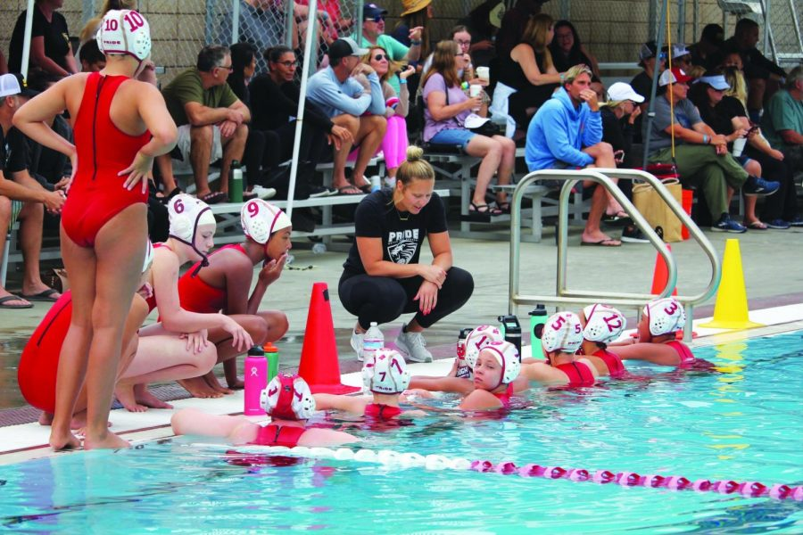 Gathering the troops: Pictured in black, new Girls Water Polo Program Head Jennifer Jamison leans over the pool during a time out to give feedback to players on her club team, Pride Water Polo Academy.