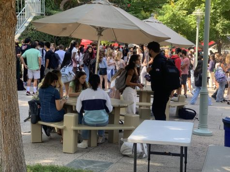 Members of the senior class convene at a table to eat during lunch.