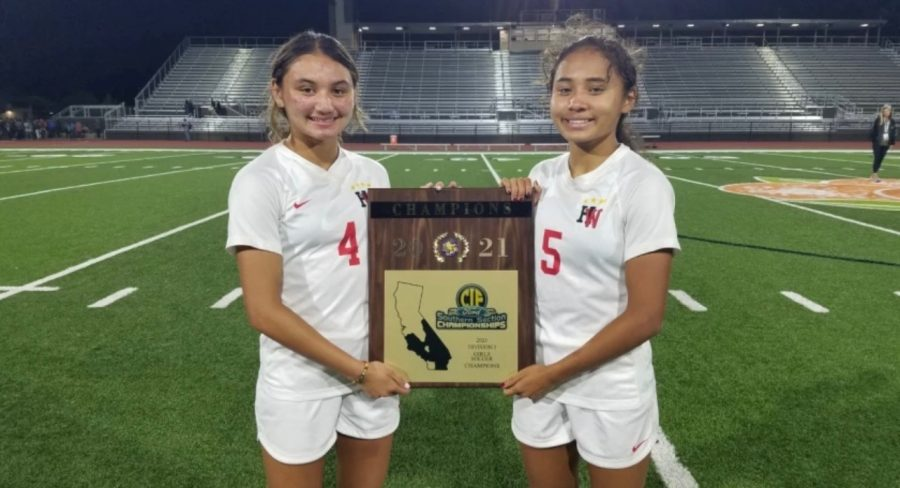 Holding the CIF SoCal State Championship trophy, the Thompson sisters pose for a photo after handling Pacifica High School 6-1