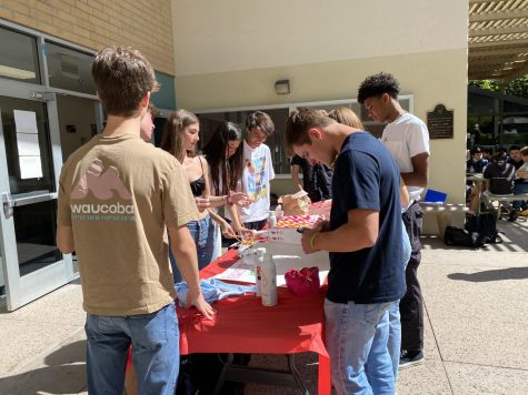 Upper school students crowd around the booth outside Chalmers to complete their registration and receive Dunkin Donuts, with their Social Security numbers in hand.
