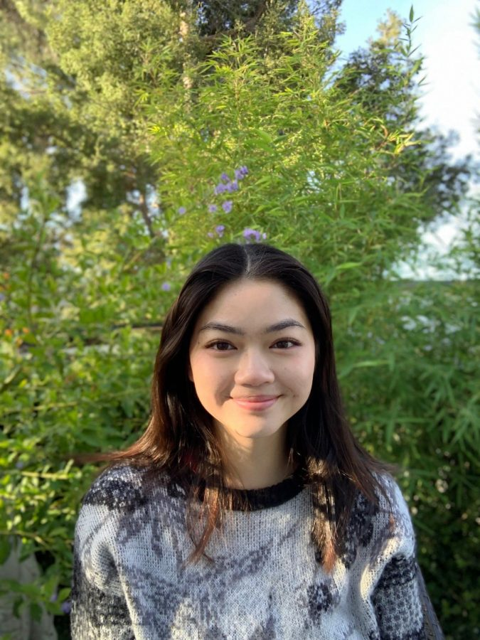 Ava Tran '22 smiles in front of shrubbery.