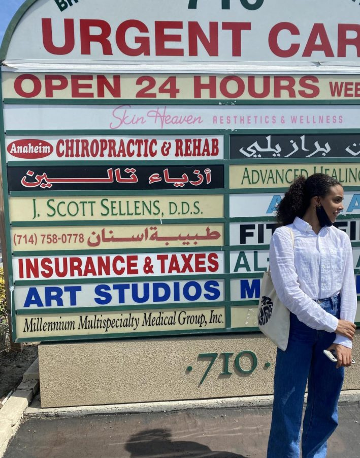 Cate+Greenman+22+stands+in+front+of+a+sign+in+Dearborn%2C+Michigan%2C+a+city+home+to+the+largest+Muslim+population+in+the+U.S.