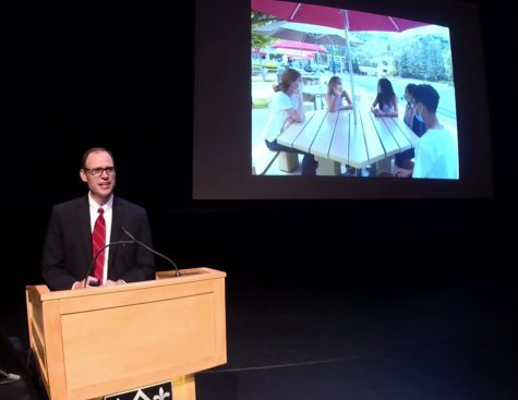 President Rick Commons presents in front of parents in the Saperstein Theater, beside a slideshow image of upper school students on the Quad.