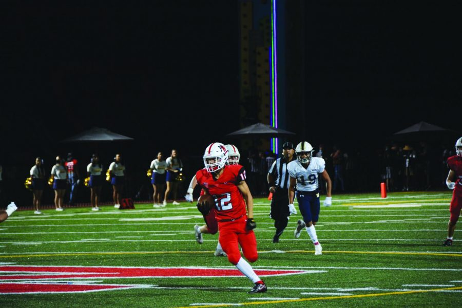 RUN IT BACK:  Surrounded by defenders, Mark Cho 22 weaves his way through the opposition, running the ball down the field in the teams 27-10 win against Mary Star of the Sea High School at Homecoming.