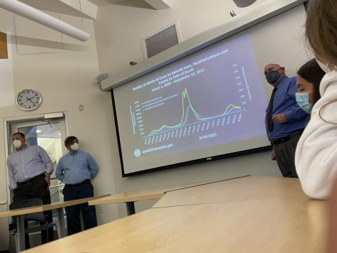 Dr. Robert Gilchick explains COVID data as part of a slideshow presented to students, as Head of the History Department and Interdisciplinary Studies Department Larry Klein and Head of Communications and Strategic Initiatives Ari Engelberg 89 look on.