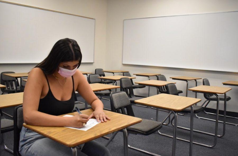 Shanti Hinkin 22 takes her test in an empty classroom.