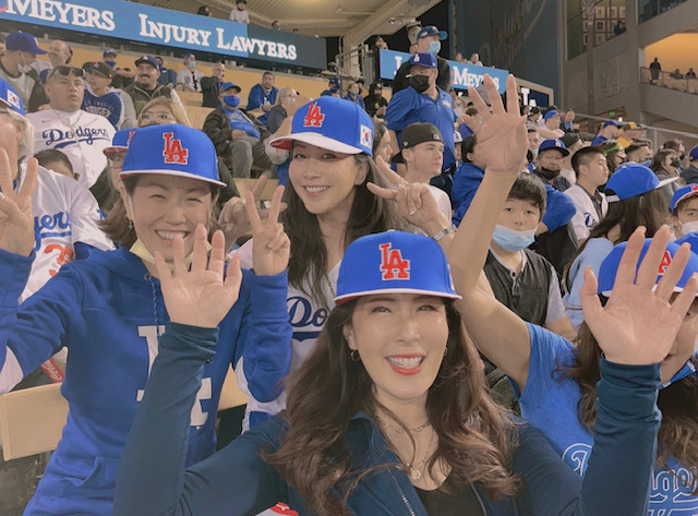 Members of the Korean American Parents Association pose in their Los Angeles Dodgers hats as they watch a game against the San Diego Padres from the stadium stands.